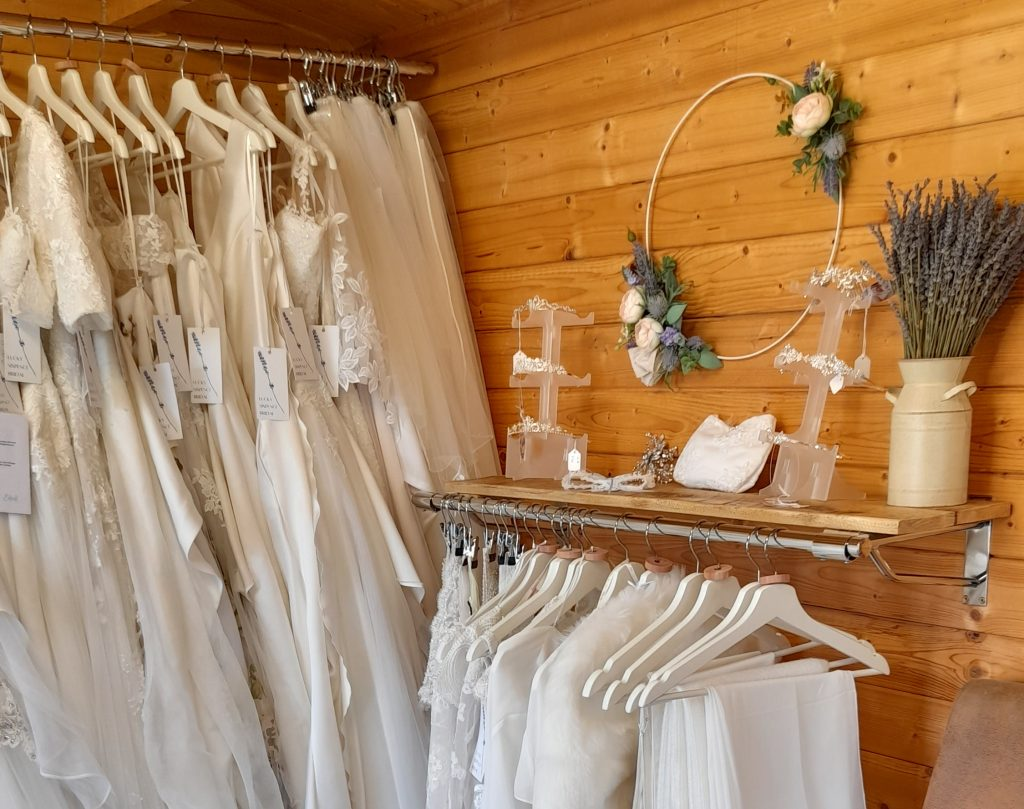 Inside Lucky Sixpence Bridal showing wedding dress rail, boleros, and other accessories.